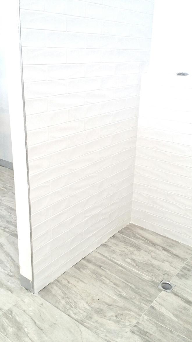 ensuite shower tiling subway tiles on wall